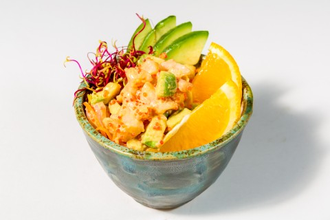 Shrimps salad with avocado and flyingfish roe served in orange